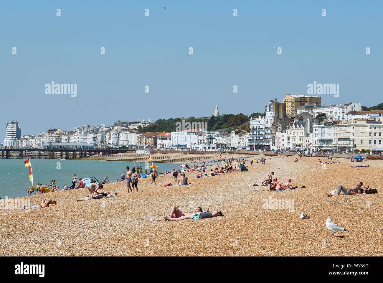 Sunbathers on Hastings Beach, East Sussex, UK in June - Stock Image