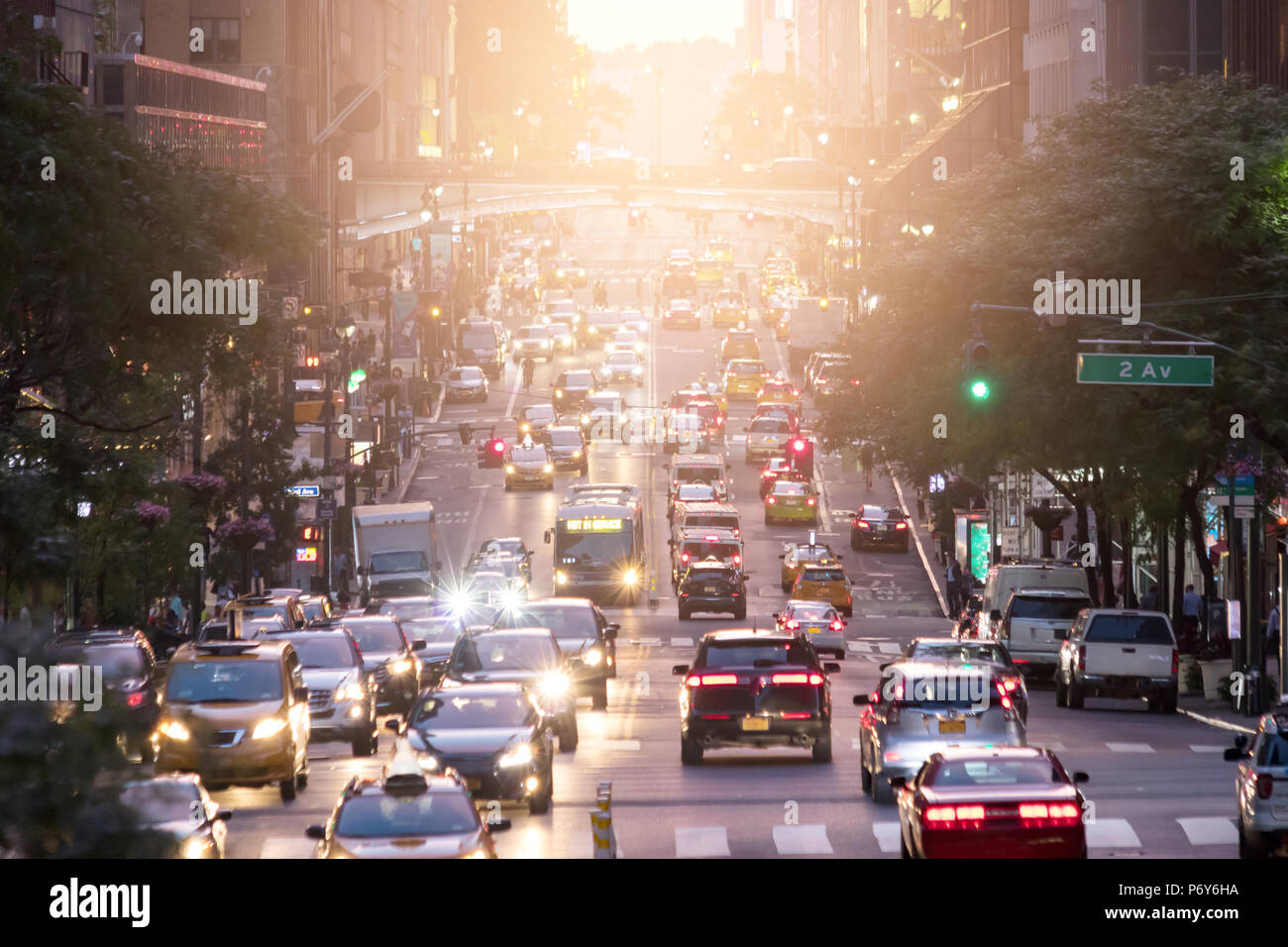 Crosstown traffic on 42nd Street in Midtown Manhattan New York City with sunlight in background - Stock Image