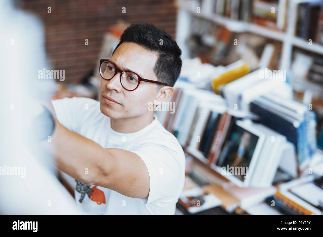 Young atrractive spectacled man drawing hand to book on a book shelf. - Stock Image