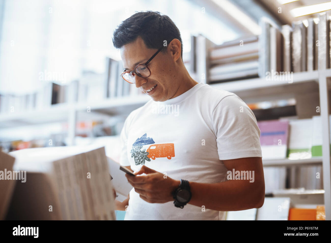 Young happy spectacled man reading book in bright modern book store. - Stock Image