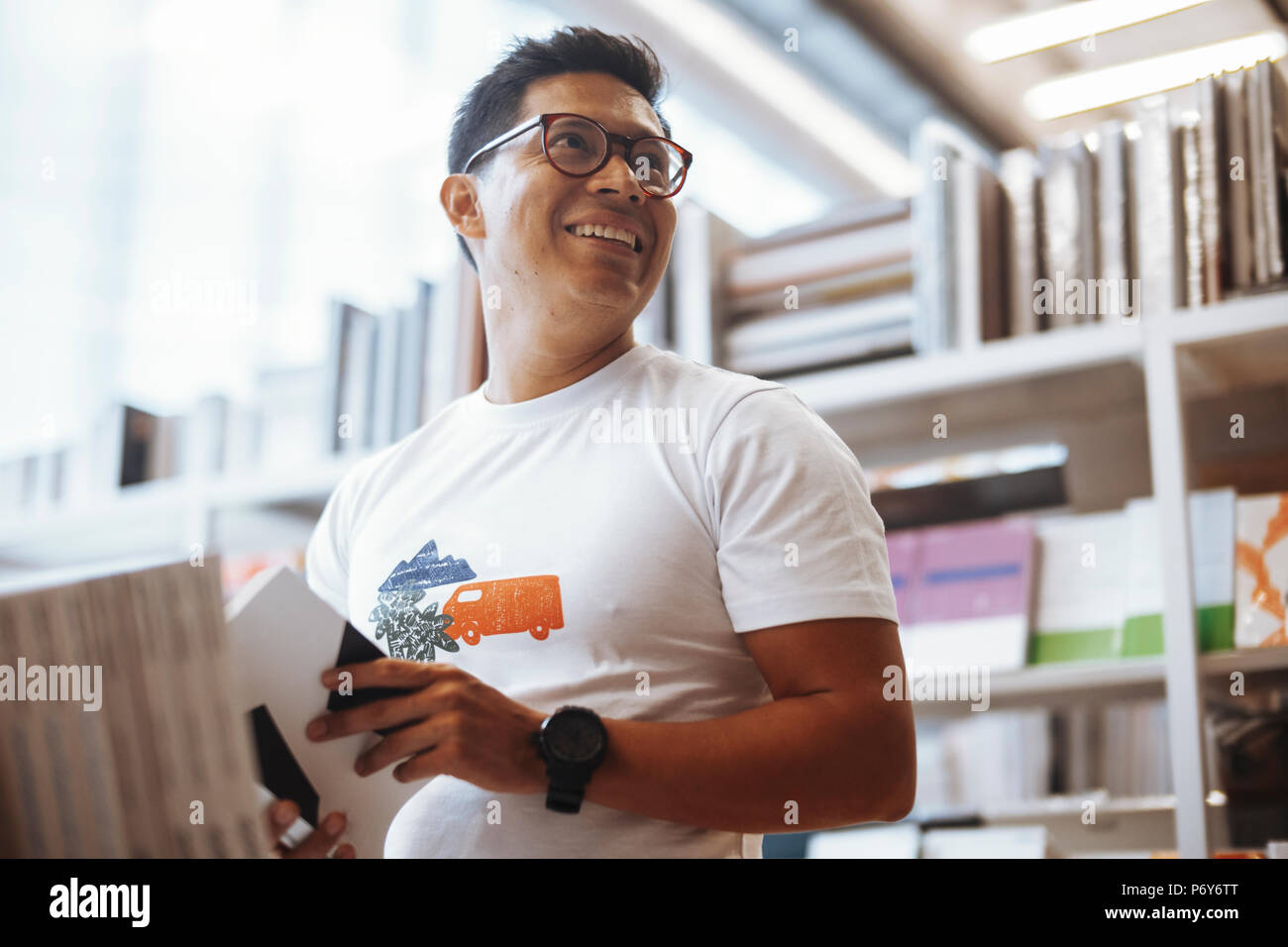Young happy man reading and looking aside in a bright modern book store. - Stock Image