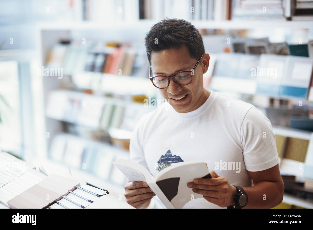 Young atrractive spectacled man reading book in a bright modern book store. - Stock Image