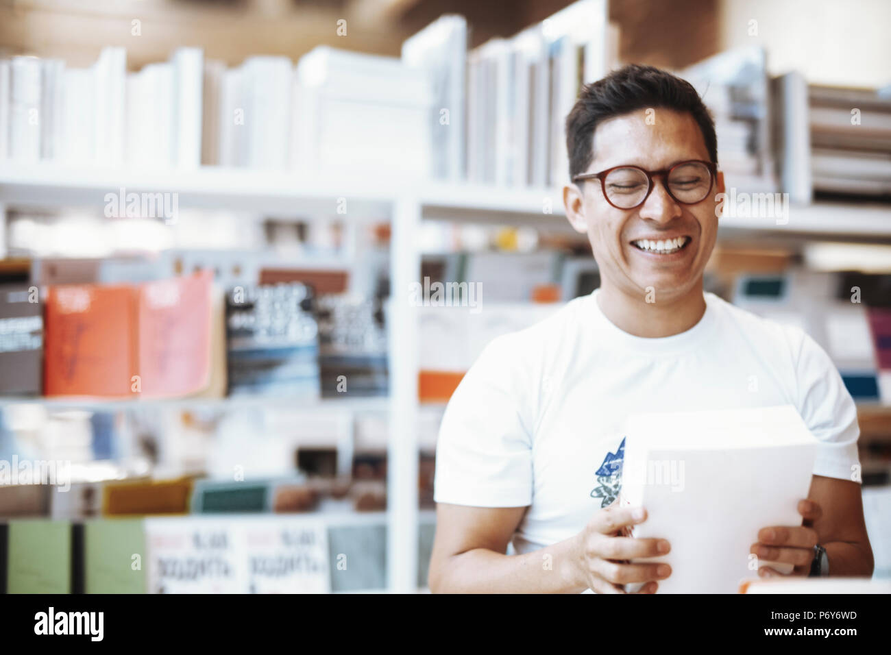Young happy spectacled man holding book with blank cover and laughing. - Stock Image