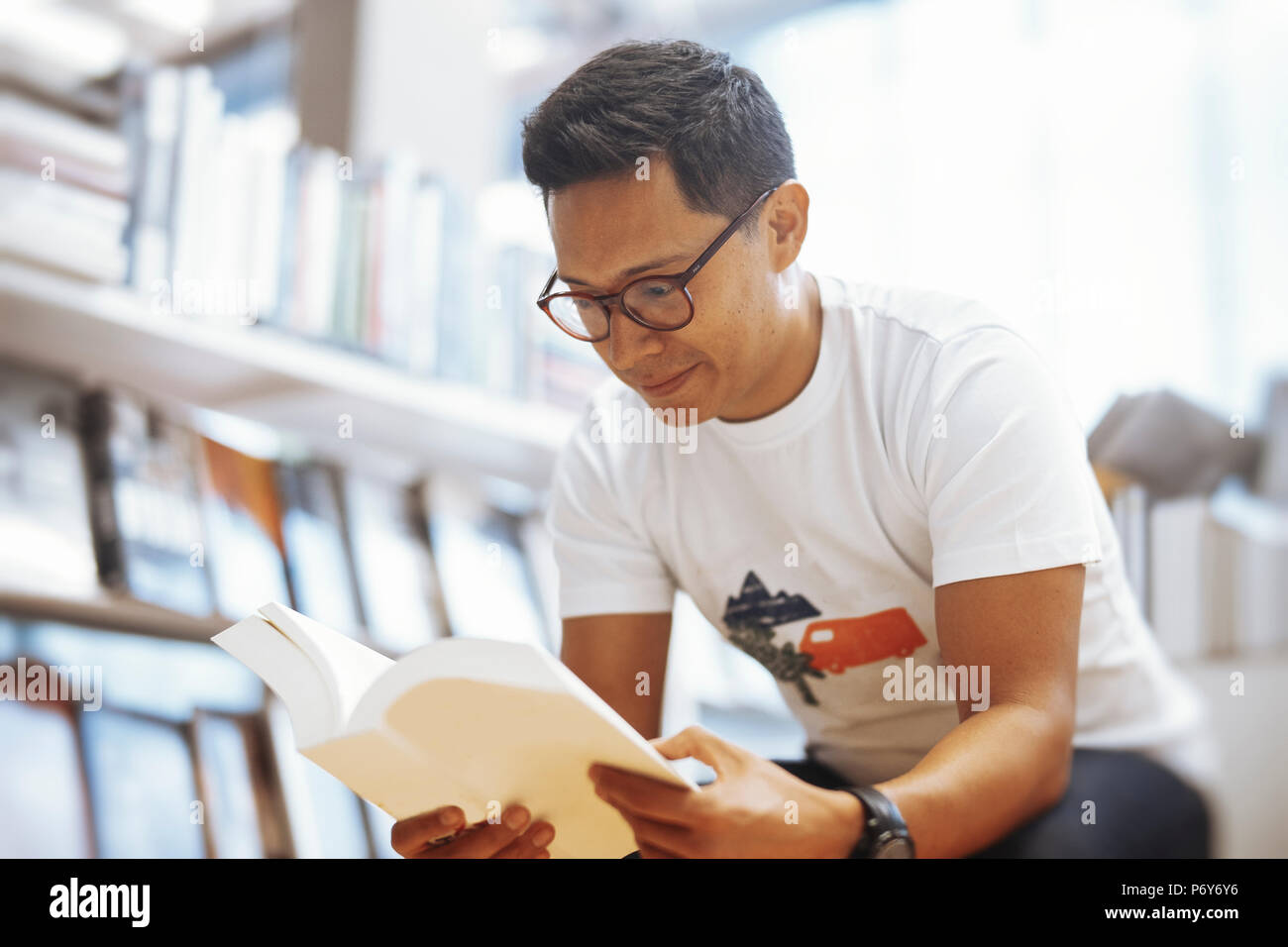 Young spectacled man sitting in a book store and reading book with blank cover - Stock Image