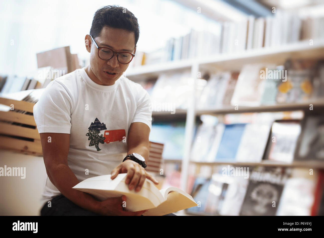 Young spectacled brunette man sitting next to book shelves and opening a book. - Stock Image