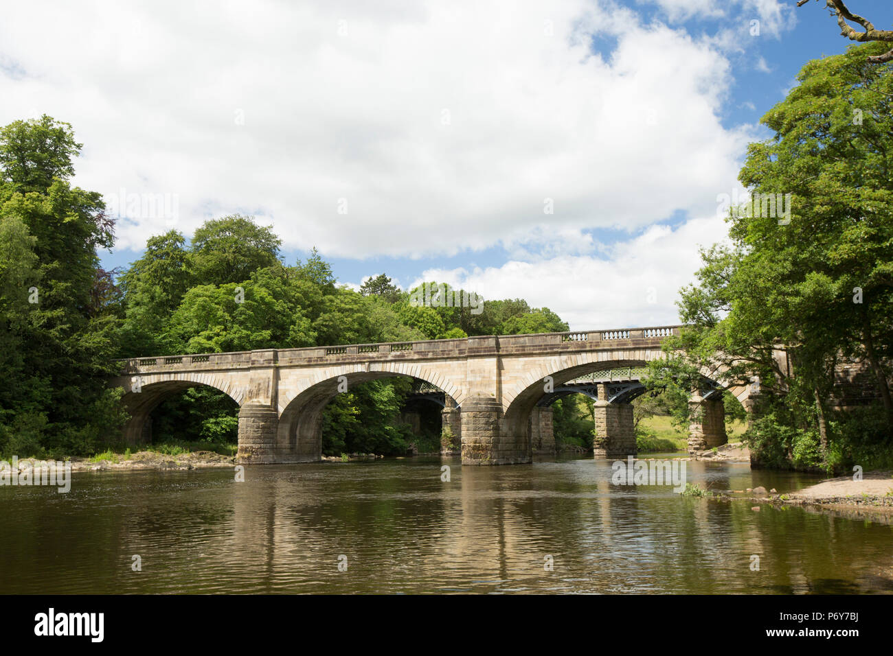 Two bridges at the River Lune at the Crook O'Lune near Caton. The nearest is a road bridge, the furthest is now a foot bridge. Lancashire England UK G - Stock Image