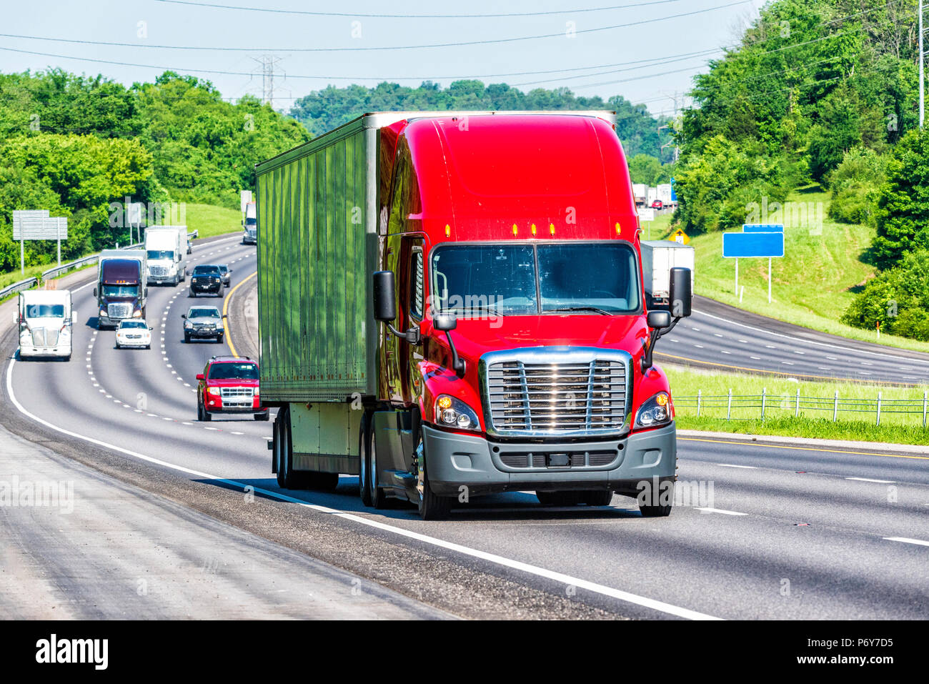 A red 18-wheeler leads other traffic down the interstate. Image shot on hot day. Heat waves from asphalt create distortion, especially on vehicles far - Stock Image