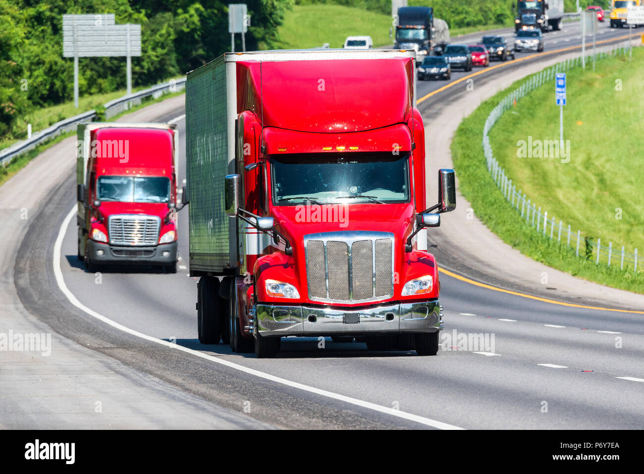 Two red trucks on a Tennessee interstate.  Image shot on hot day. Heat waves from asphalt create distortion, especially on vehicles farther from the c - Stock Image