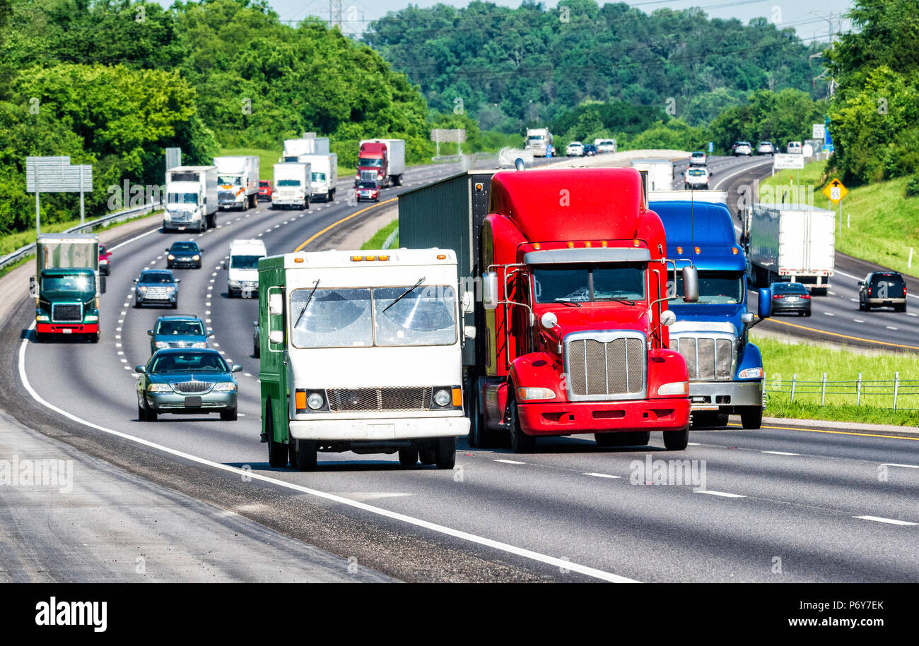 American colors reflect in three trucks leading traffic on an interstate highway. Shot on hot day. Asphalt heat waves cause distortion on vehicles far - Stock Image