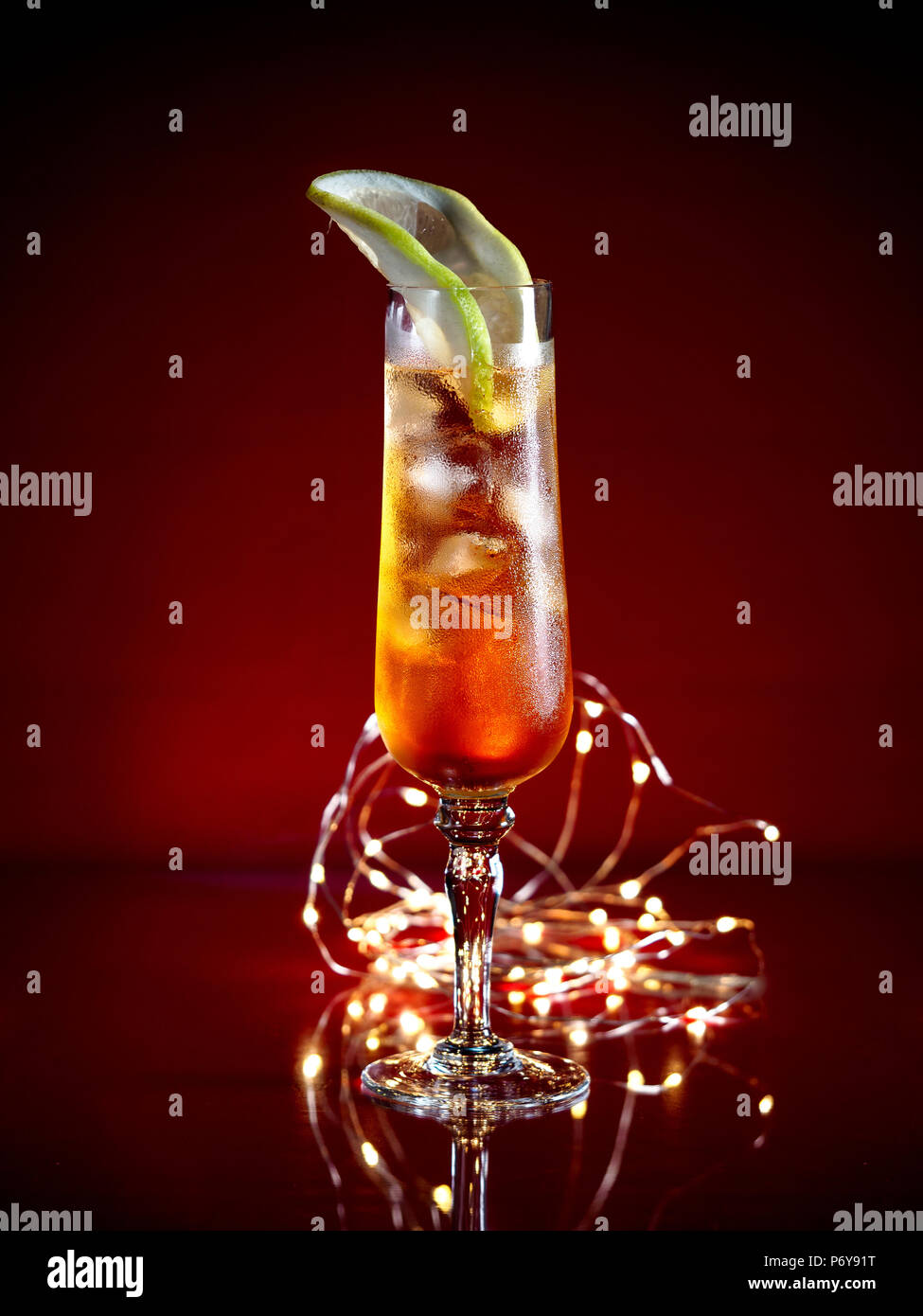 Aperol Spritz garnished with a grapefruit slice served in a tall glass on a dark background with festive lights - Stock Image