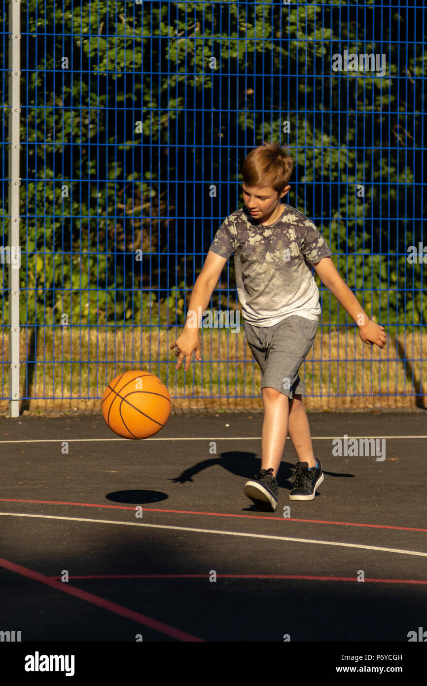Pre-teen boy playing with a basketball in a park - Stock Image