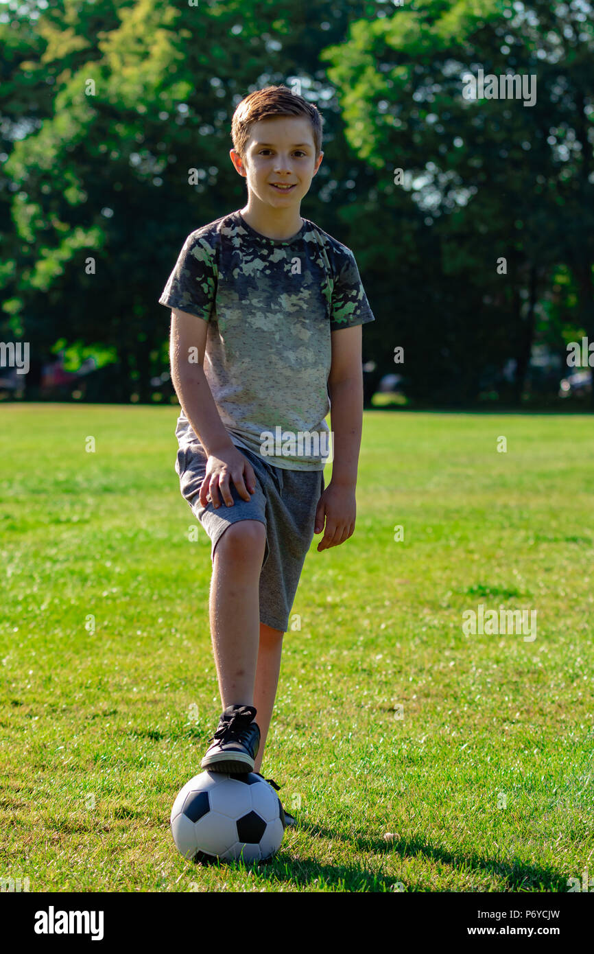 Pre-teen boy with a football in a park Stock Photo