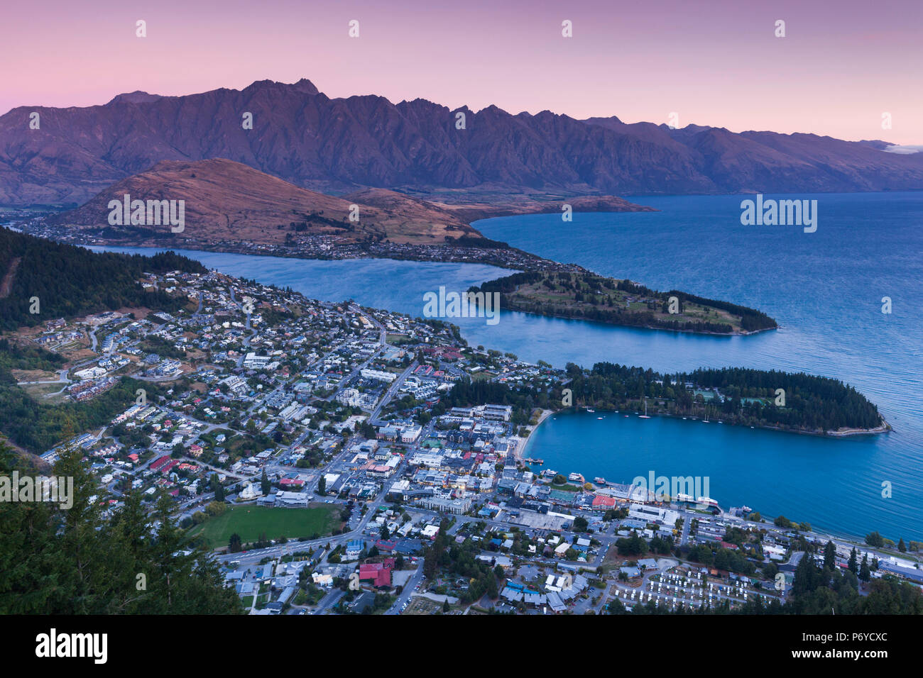 New Zealand, South Island, Otago, Queenstown, elevated town view with The Remarkables from the Skyline Gondola deck, dusk - Stock Image