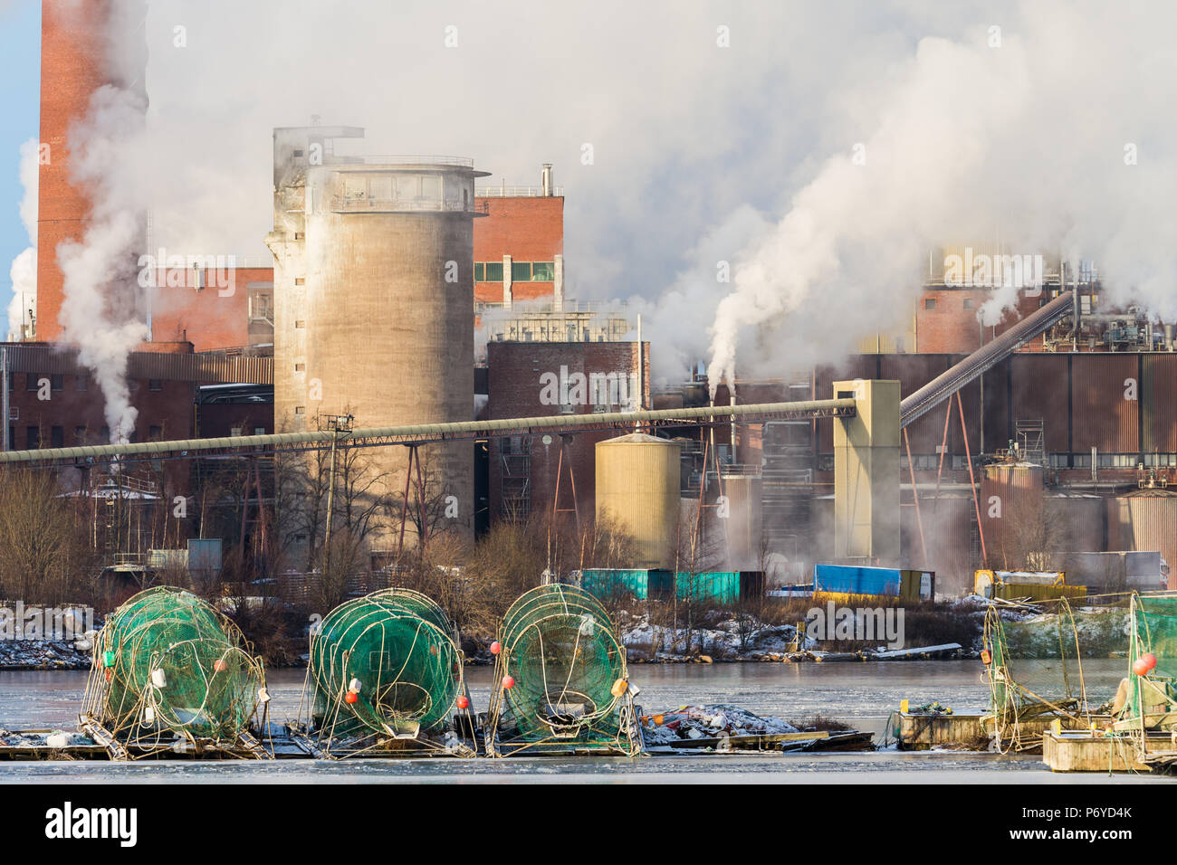 Green fykenets in front of steaming factory on sunny day - Stock Image