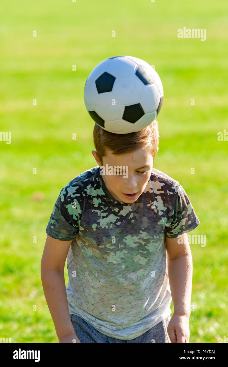 Pre-teen boy playing football in a park - Stock Image