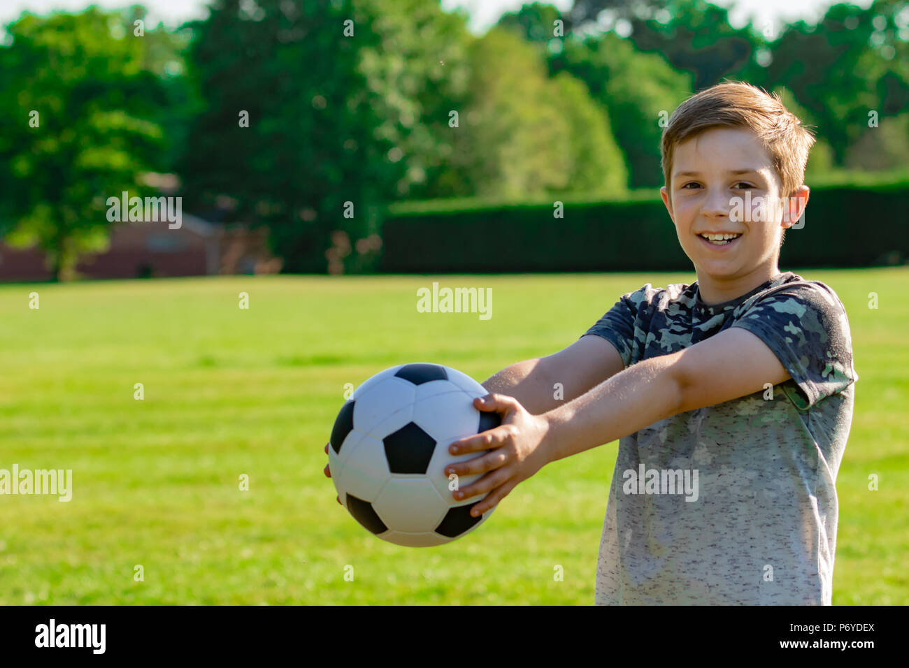 Pre-teen boy holding a football in a park - Stock Image