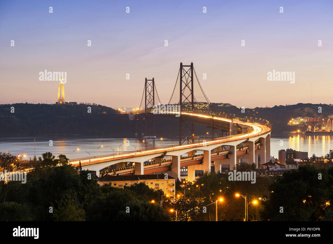 25 de April bridge (similar to the Golden Gate bridge) across the Tagus river and Cristo Rei (Christ the King) on the south bank of the river, in the evening. Lisbon, Portugal - Stock Image