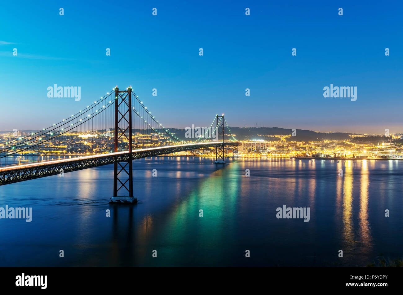 25th of April Bridge over the Tagus river (Tejo river) and Lisbon at twilight. Portugal - Stock Image