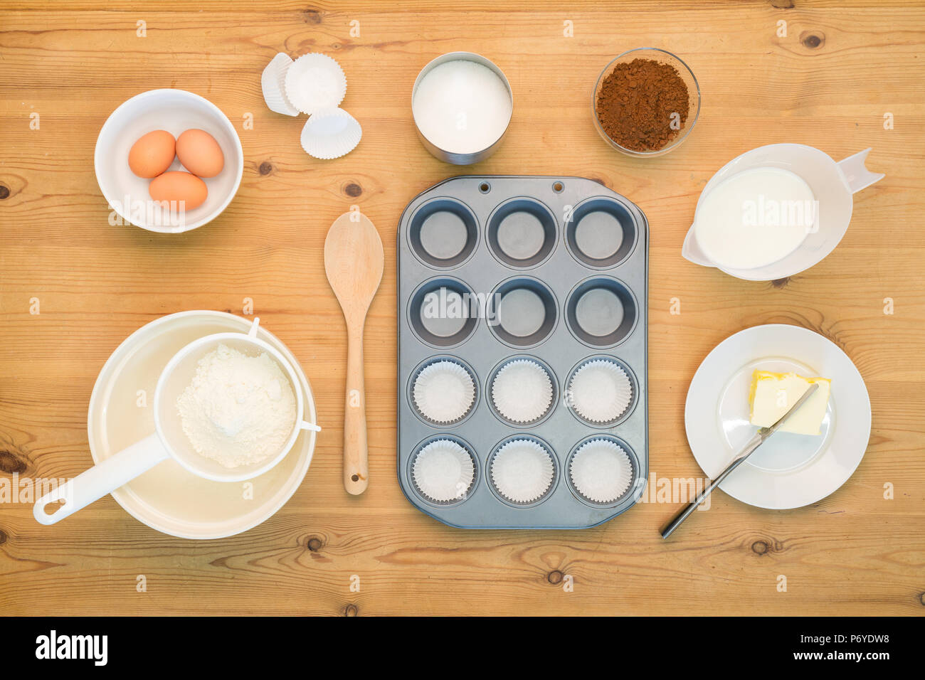 Overhead flat lay arrangement of Cup Cake making ingredients and equipment on a kitchen table. - Stock Image