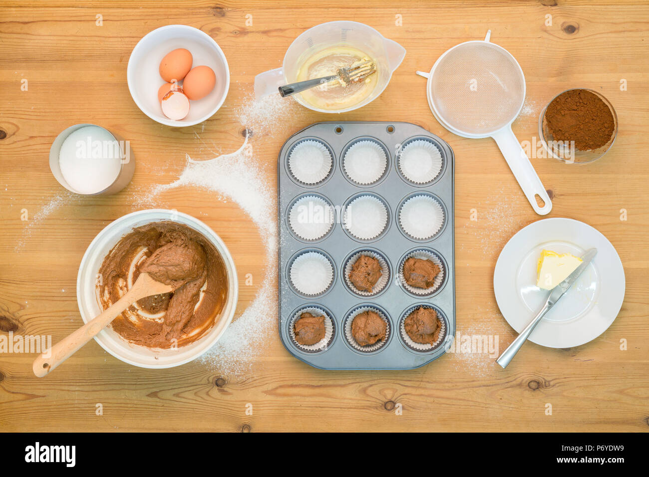 Overhead flat lay arrangement of Cup Cake making mixture and equipment on a kitchen table. - Stock Image