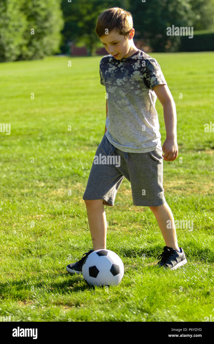 Pre-teen boy playing with a football in a park - Stock Image