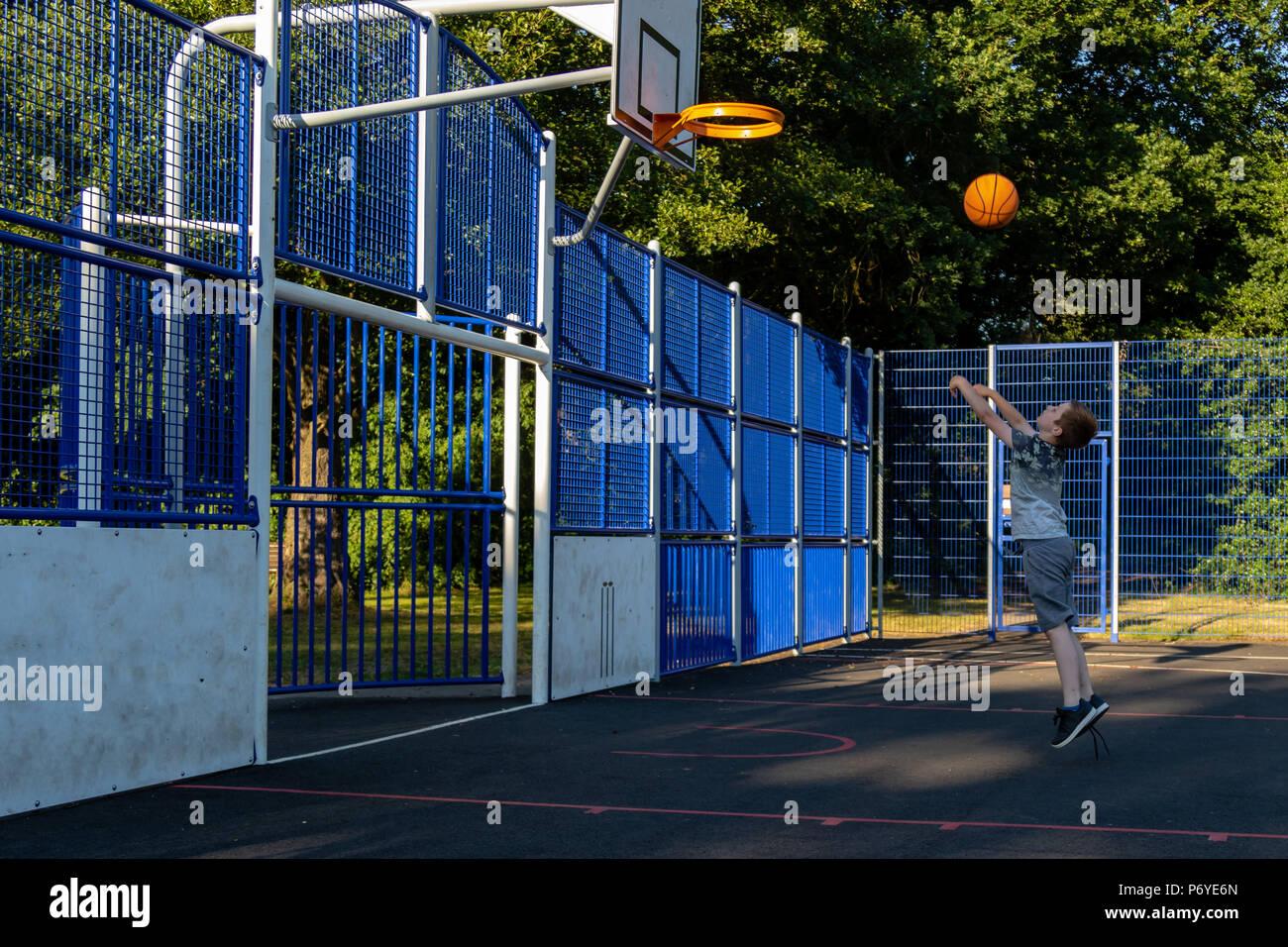 Pre-teen boy shooting basket ball in a park - Stock Image