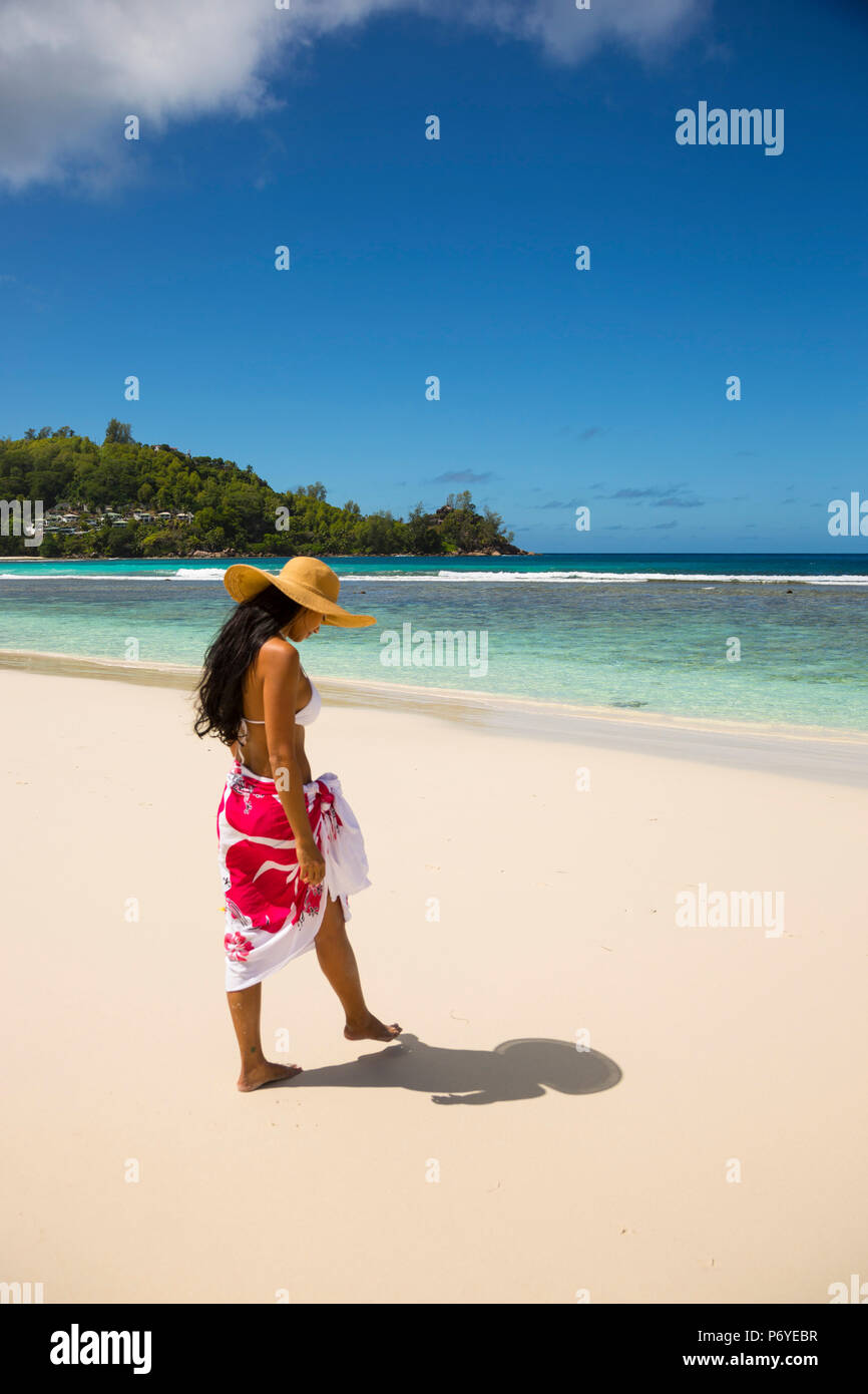 Young woman sitting on the beach on Mahe, Seychelles - Stock Image