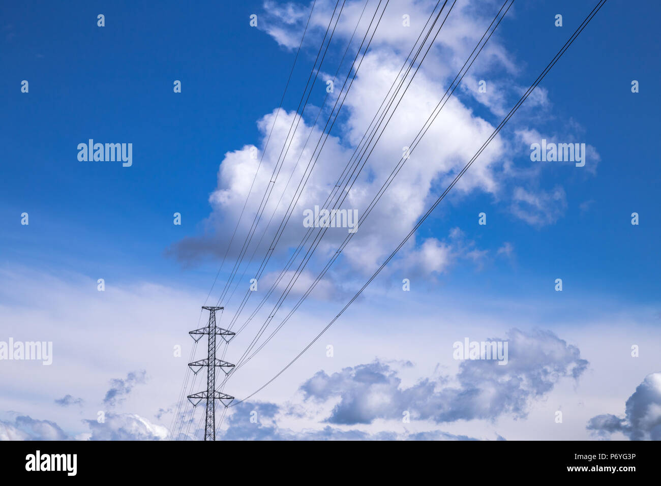 Electric cabels / powerlines and pylon in front of deep blue sky with clouds - Stock Image