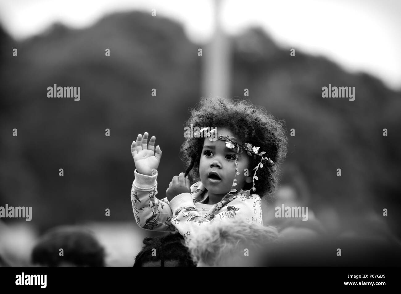 Monochrome image of a beautiful mixed race baby girl sitting on an adult's shoulders at the 2018 Africa Oye music festival in Sefton Park, Liverpool. - Stock Image