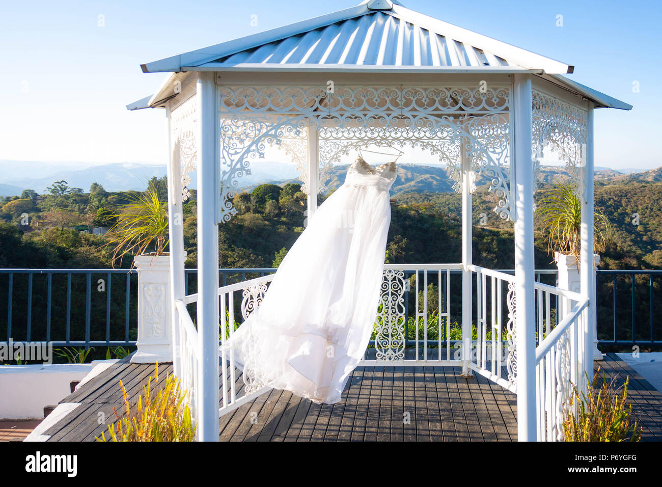 A white wedding dress hanging underneath a white gazebo blowing in the breeze with a view of the Thousand Hills in KwaZulu Natal, South Africa. Stock Photo