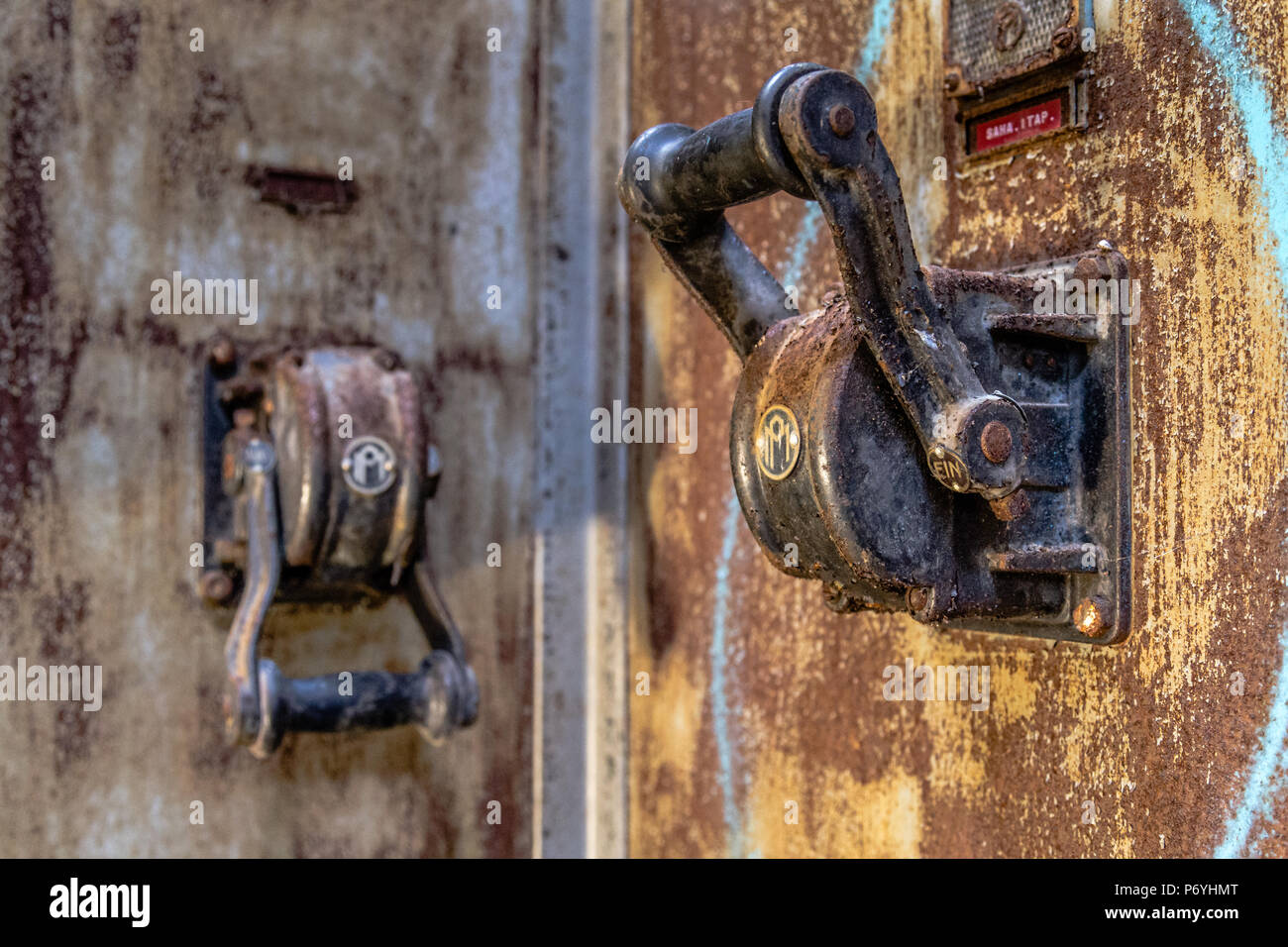 Two sturdy and rusty machine levers in old abandoned factory - Stock Image