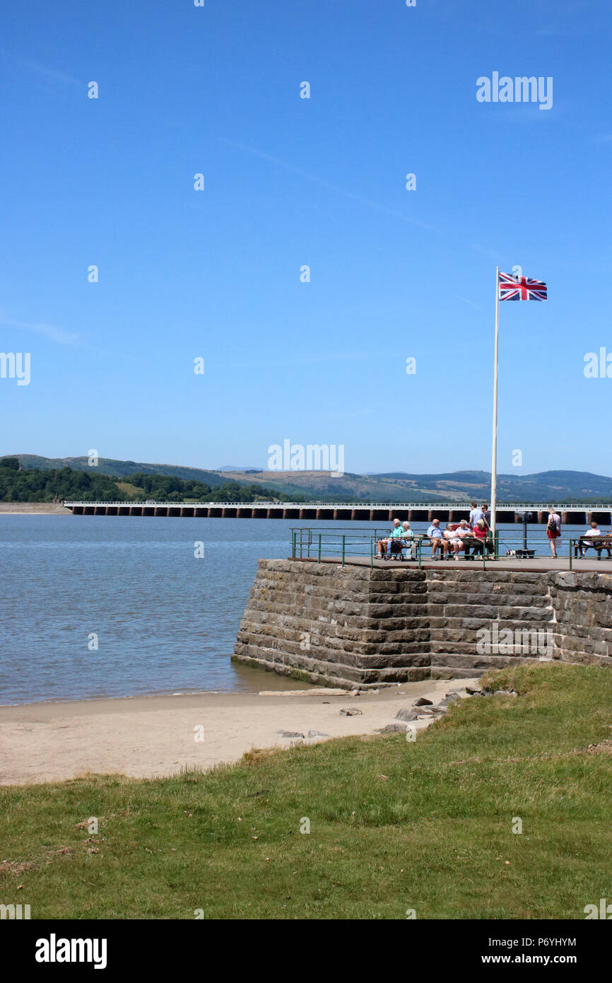 People on Arnside Pier by the River Kent estuary as the tide comes in with Arnside railway viaduct behind and the Union Flag flying on the flagpole. - Stock Image