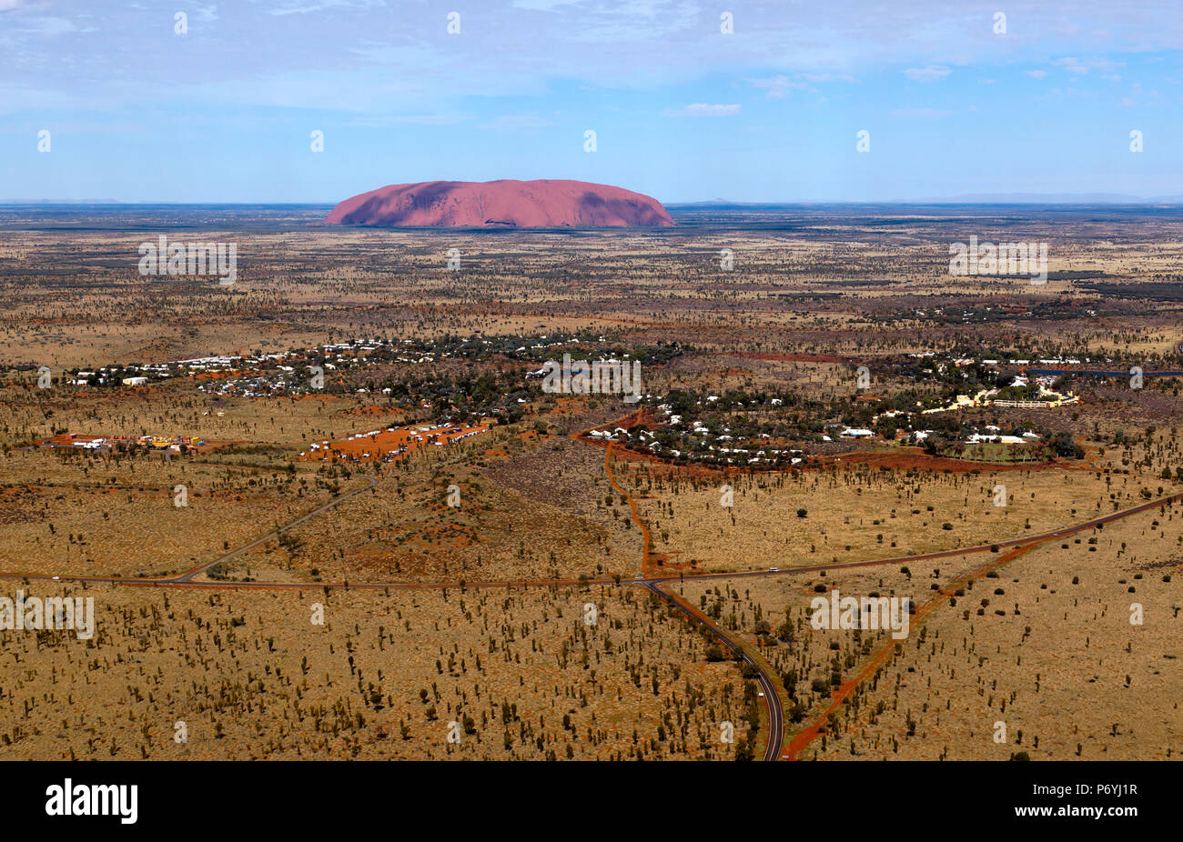 Aerial view of  the town of Yulara with Uluru in the background - Stock Image