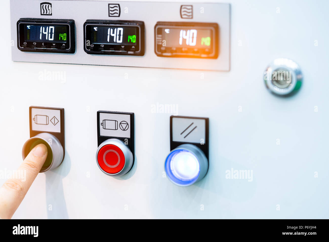 Engineer's hand push green button to open temperature control machine. Temperature control panel cabinet contain digital screen display for temperatur - Stock Image