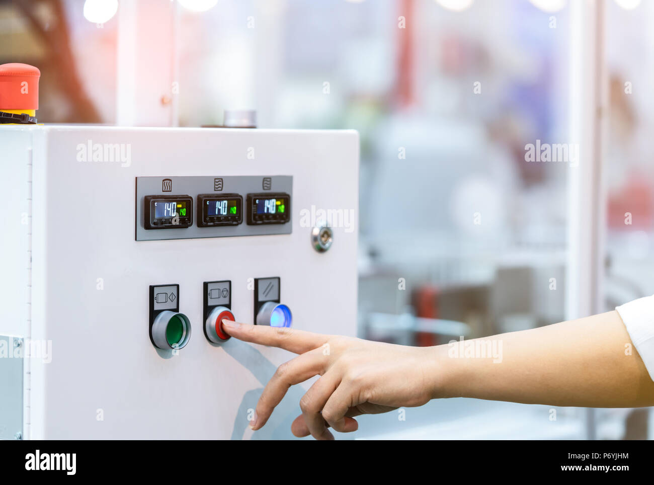 Engineer's hand push red button to shutdown temperature control machine. Temperature control panel cabinet contain digital screen display for temperat - Stock Image
