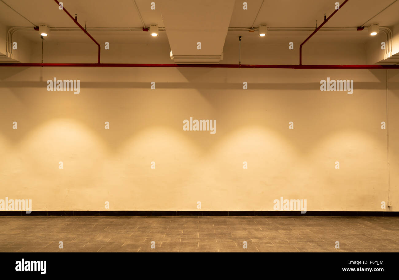Empty Room And White Wall With Spotlights. Illuminated Lamp Light. Room  Interior With Ceiling Lamp Light And Colorful Wall. Empty Tile Floor