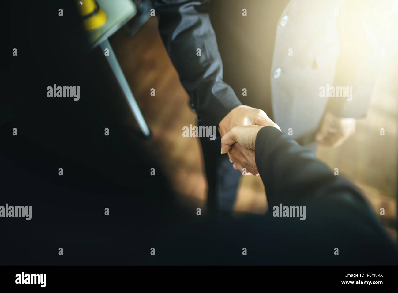 Business handshake and business people.Vintage tone Retro filter effect,soft focus,low light. handshake in office. success concept. - Stock Image