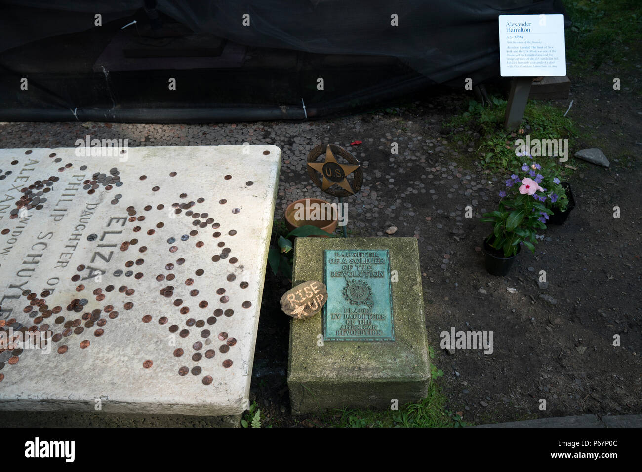 Alexander Hamilton's grave in the churchyard of Trinity Wall Street is shrouded in netting for cleaning, but the grave of his wife, Eliza, is visible. - Stock Image