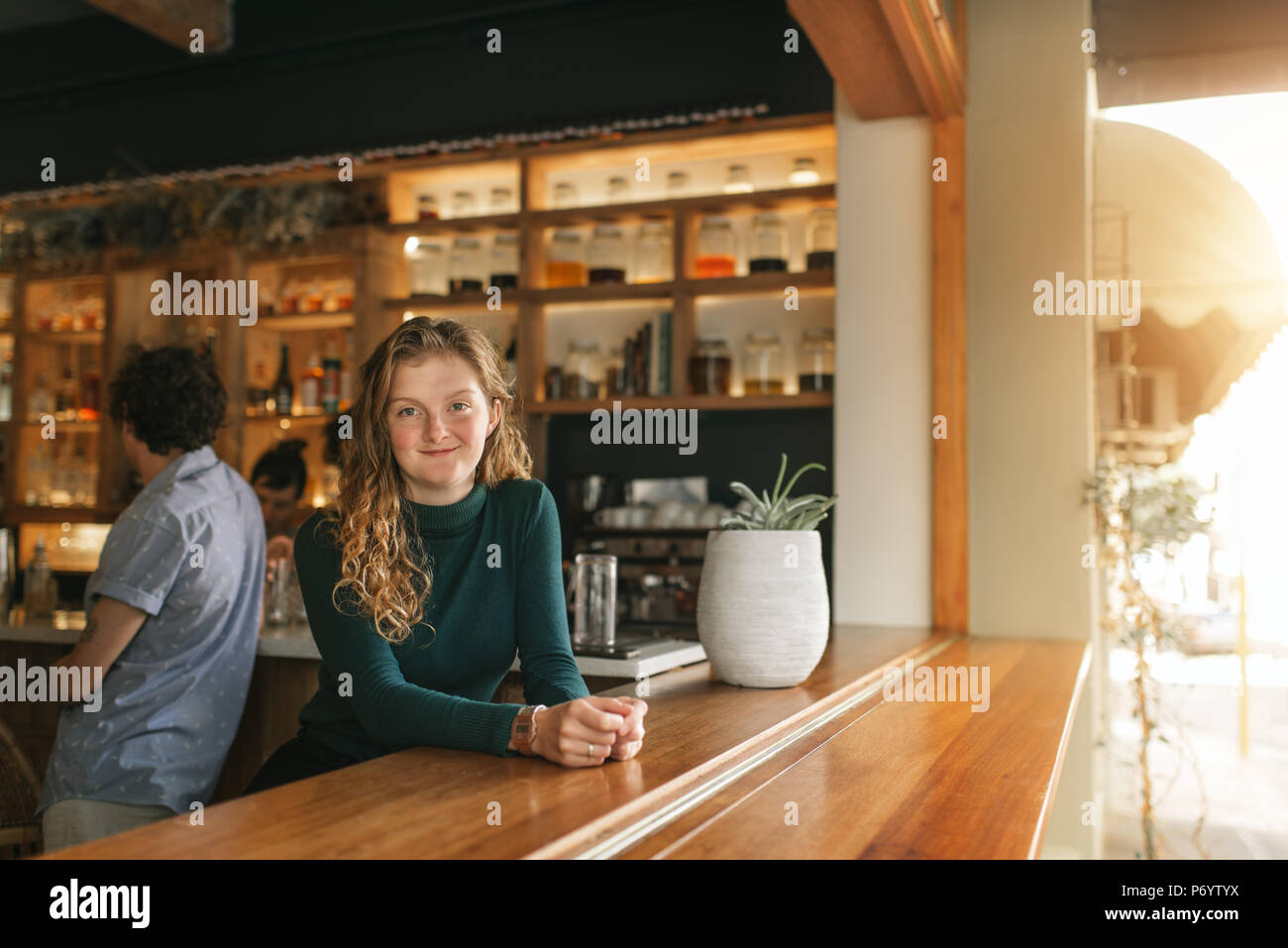 Friendly waitress leaning on the counter of a trendy bar - Stock Image