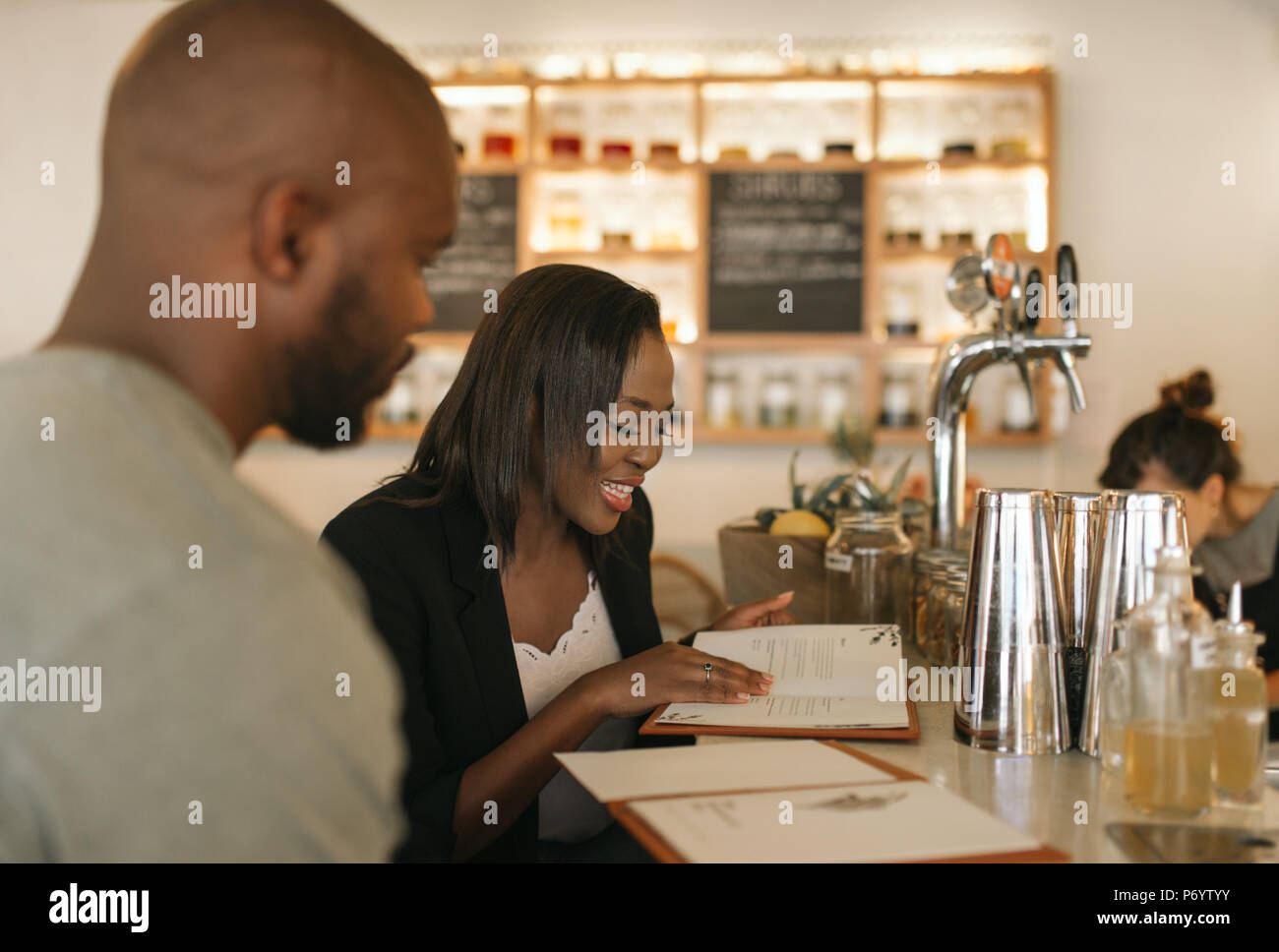 Smiling young African American couple reading menus in a bar - Stock Image