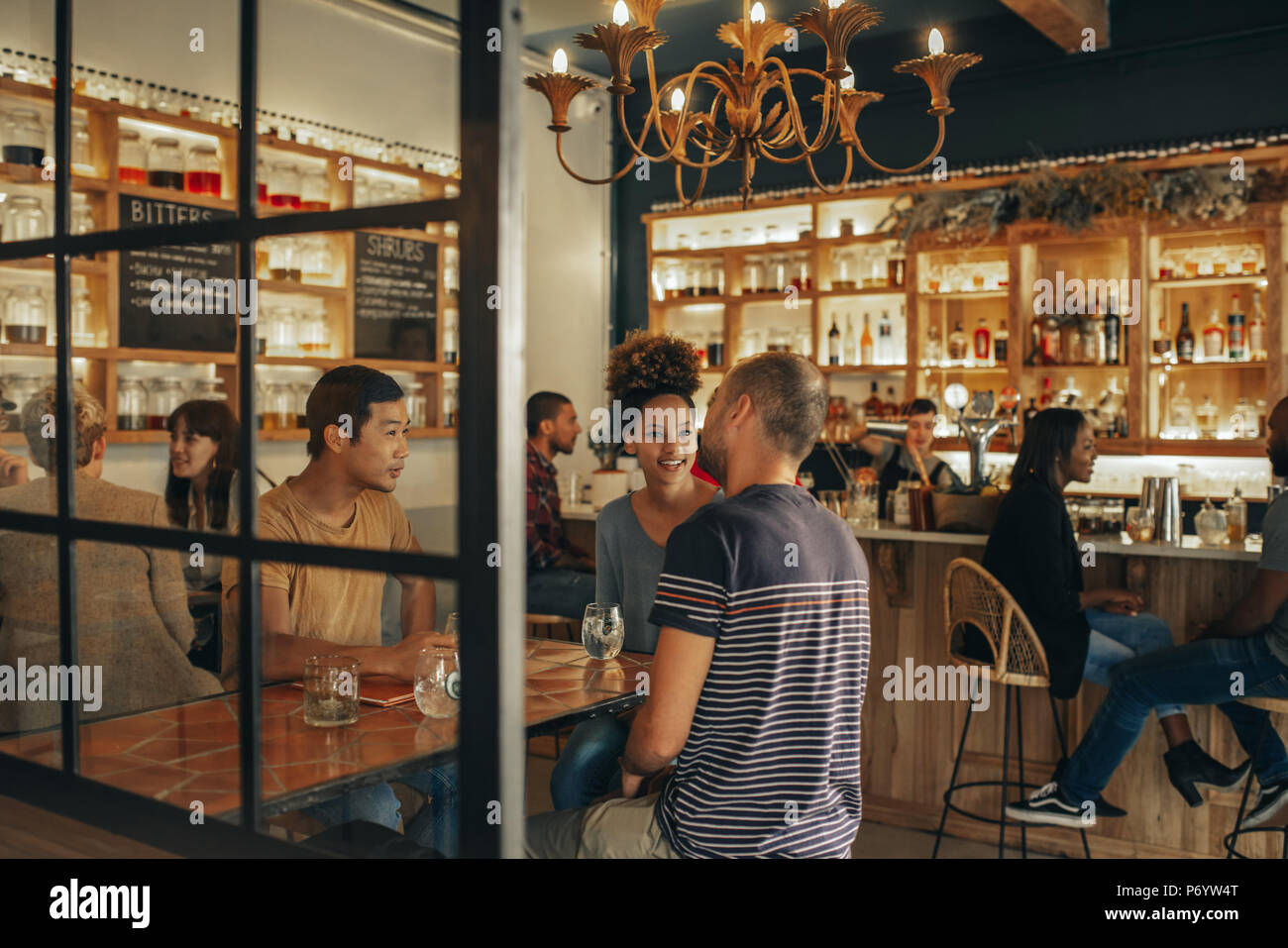 Diverse young friends sitting in a bar having drinks together - Stock Image