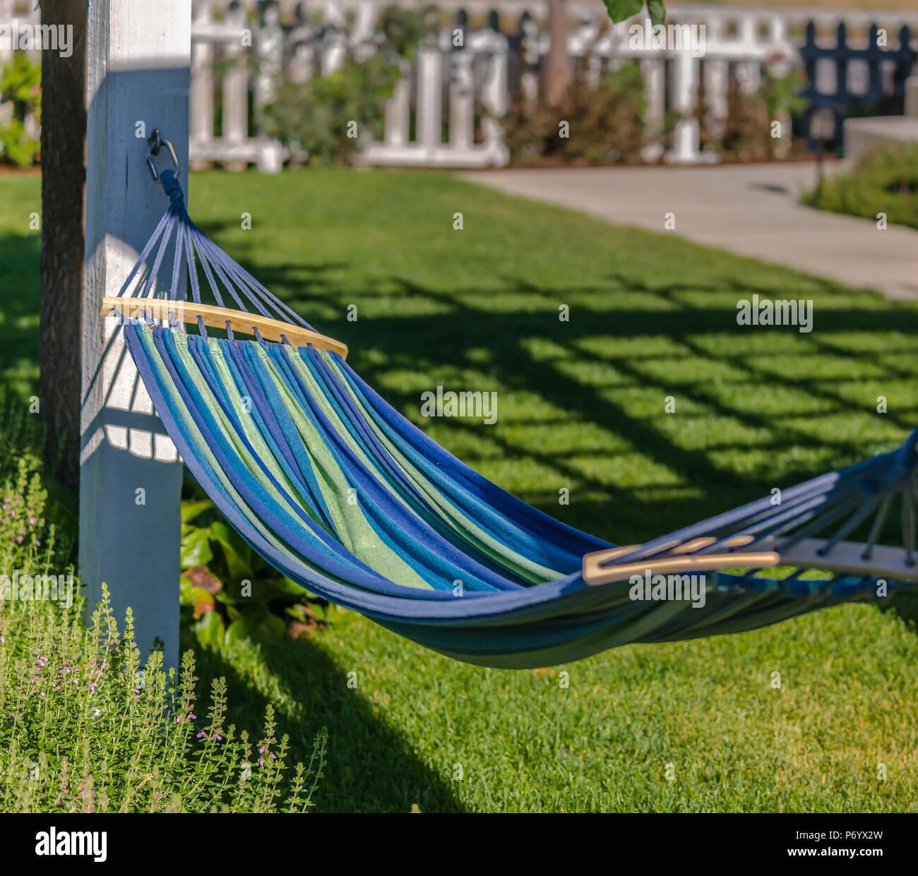 Hammock in beautiful backyard with lawn - Stock Image