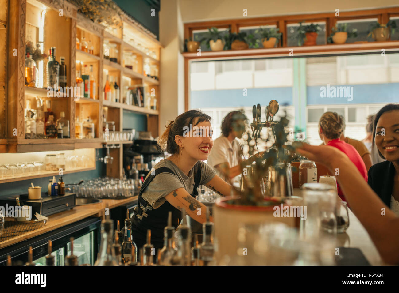 Smiling female bartender talking with customers at a bar counter - Stock Image