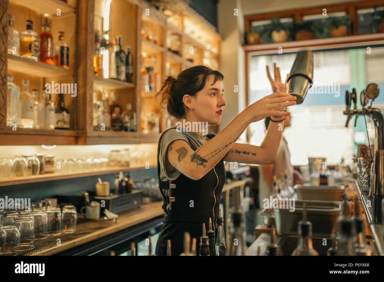 Young female bartender mixing cocktails behind a bar counter - Stock Image