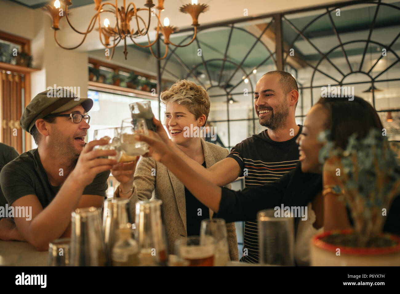 Group of friends cheering with drinks in a trendy bar - Stock Image