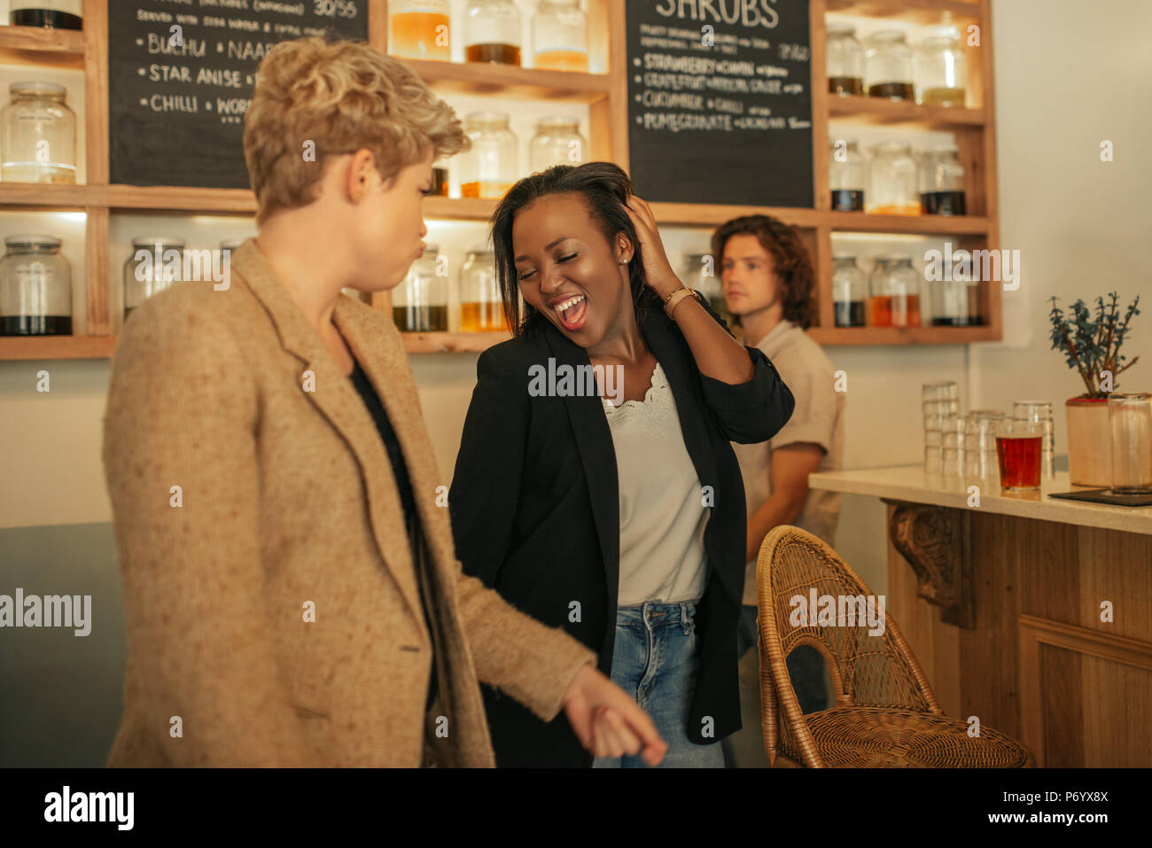 Two laughing girlfriends dancing together in a bar - Stock Image