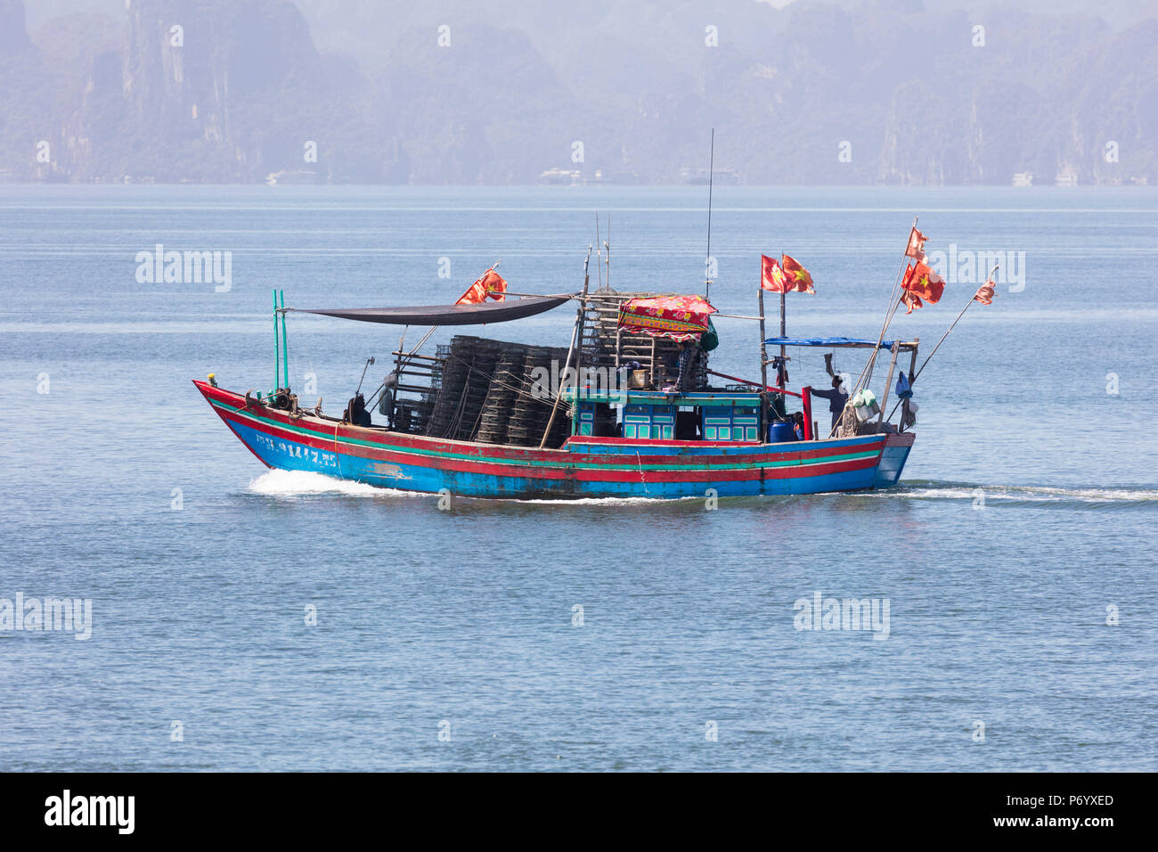 Colourful fishing boat with flags, Halong Bay, Quang Ninh Province, North-East Vietnam, South-East Asia Stock Photo