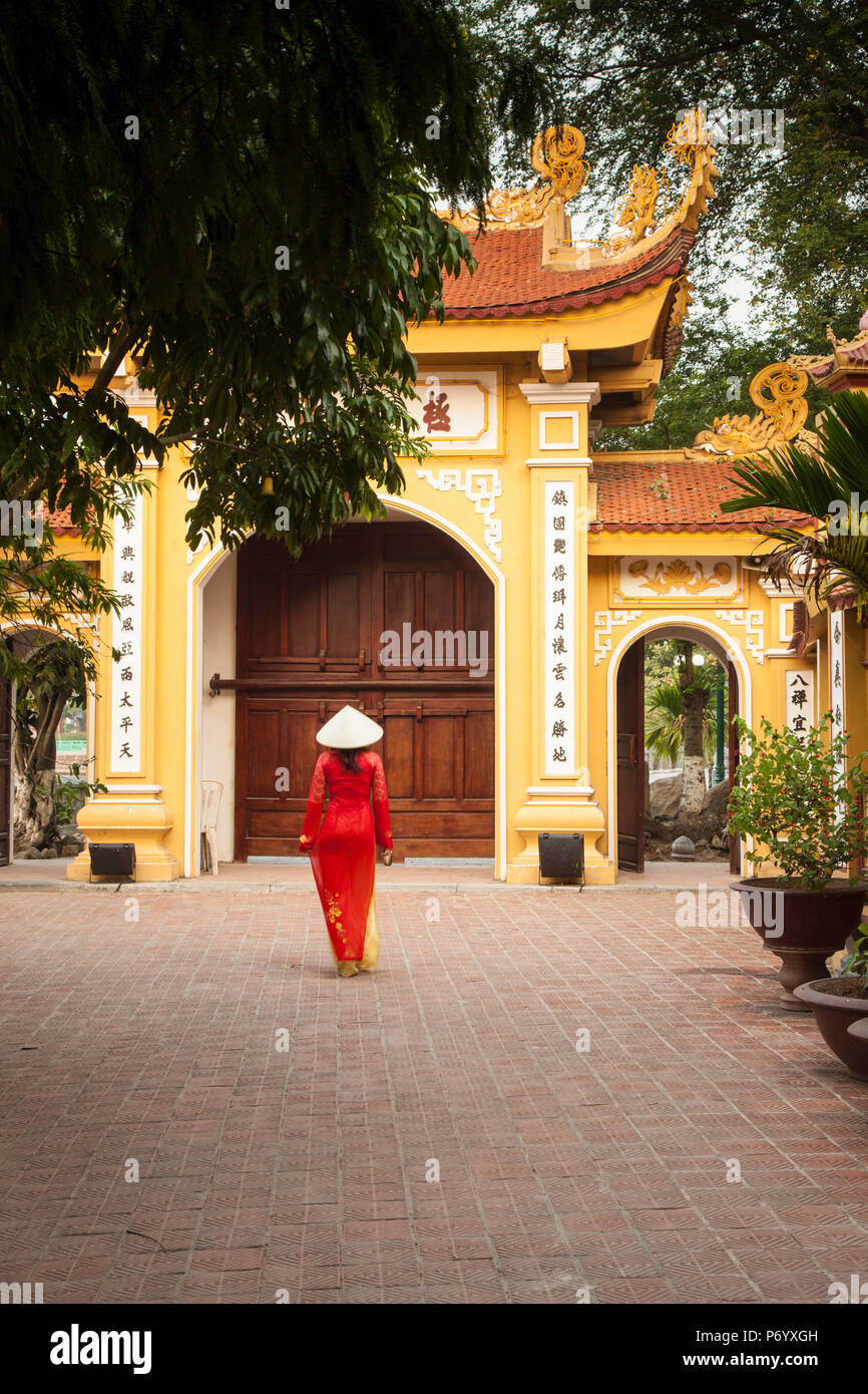 Girl wearing Ao Dai dress, Tran Quoc Pagoda, West Lake (Ho Tay), Hanoi, Vietnam (MR) - Stock Image