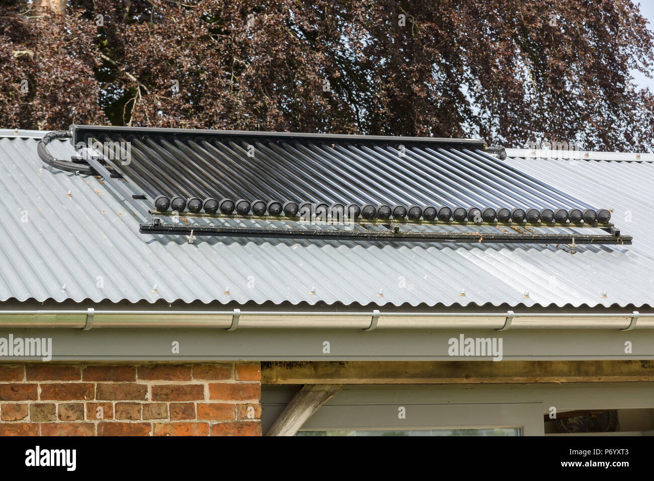 Solar heating panels or collectors on a building roof used to provide energy efficient domestic hot water - Stock Image