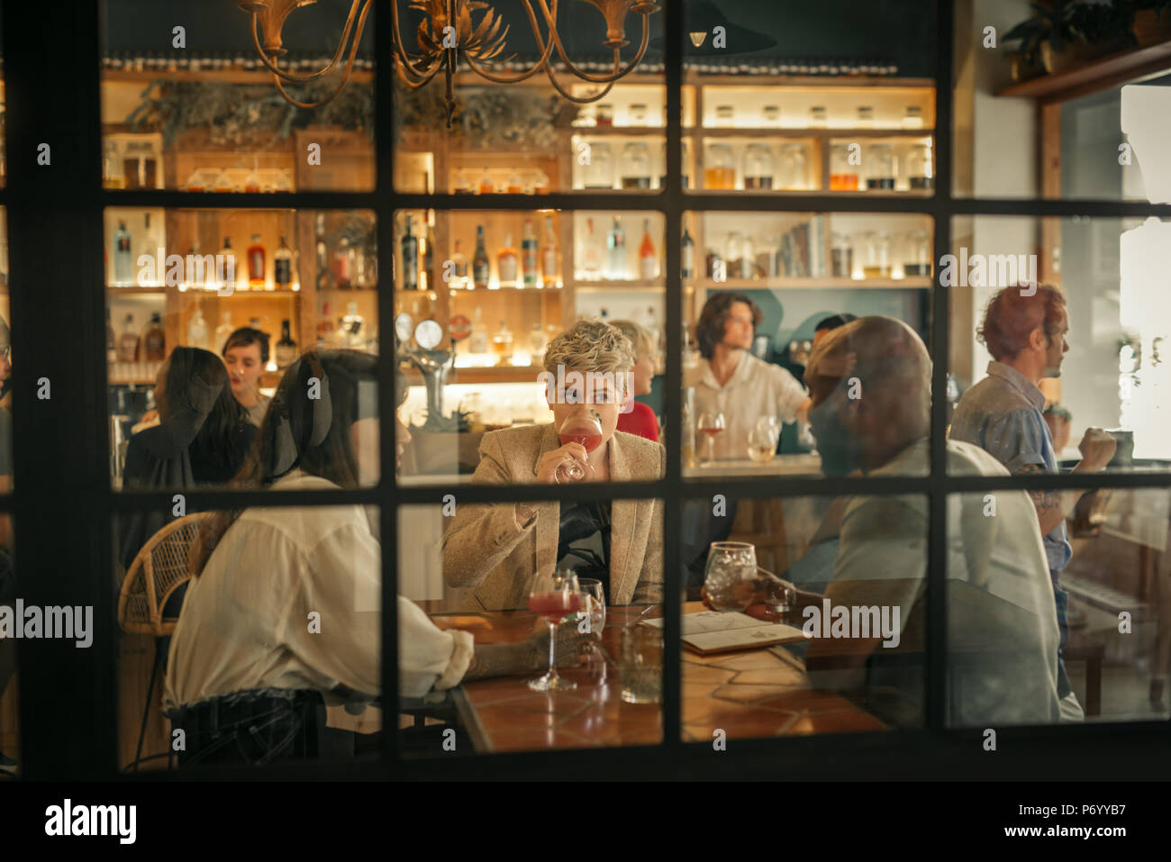 Diverse young friends having drinks together at a trendy bar - Stock Image